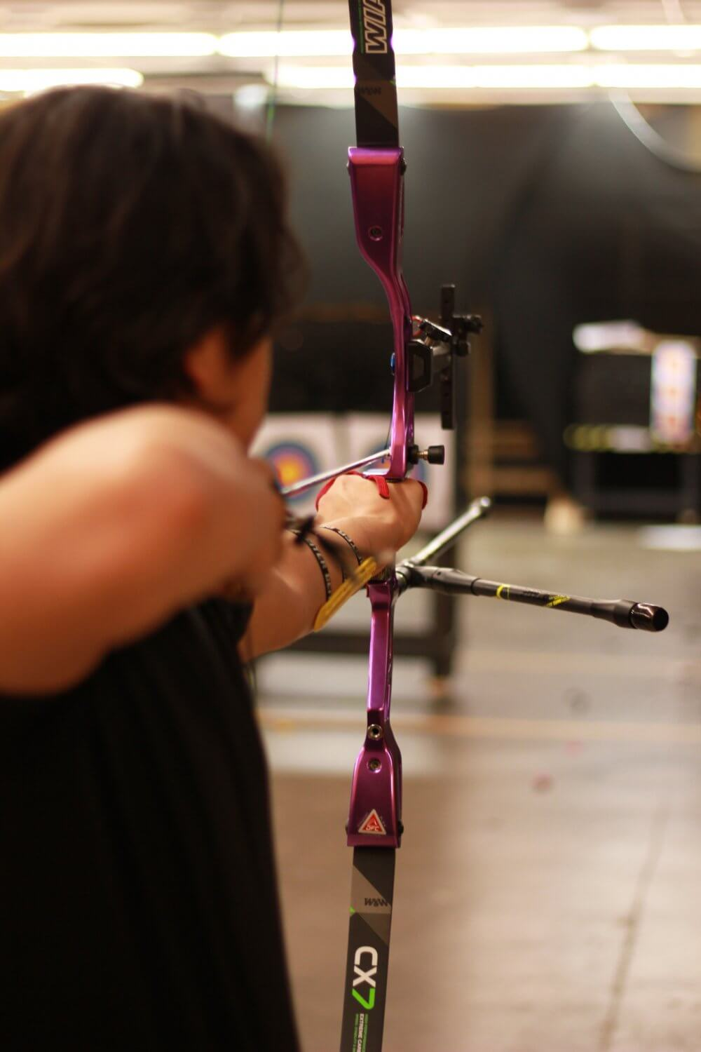 Man shooting archery compound bow, view from behind