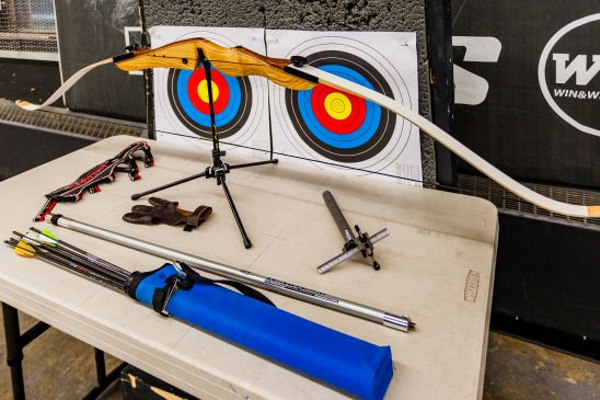 Displaying Archery Equipment on table, Bow, arrows, targets, quiver, arm guard and glove